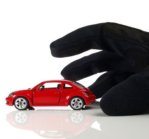 picture of glove reaching for red toy vehicle in the appearance that it will be stolen